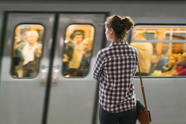 At The Subway Station Young woman standing on the subway station and waiting for her train. subway platform stock pictures, royalty-free photos & images