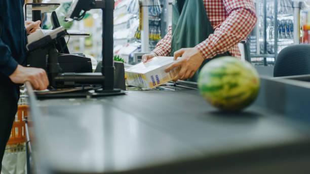 bij de supermarkt: checkout counter handen van de rijkskassier scant boodschappen, fruit en andere gezonde voedingsmiddelen. schoon modern winkelcentrum met vriendelijk personeel, kleine lijnen en tevreden klanten. - lopende band stockfoto's en -beelden