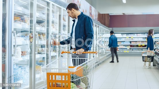 At the Supermarket: Handsome Man Pushes Shopping Card and Browses for Products in the Frozen Goods Section. Man Looks into Glass Door Fridge, Looking for Dairy Products. Other Customer Shopping in the Background.