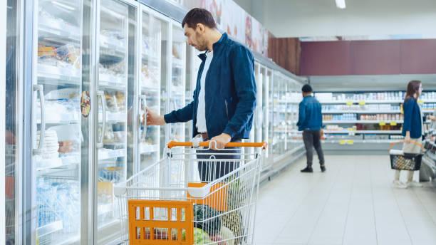 no supermercado: homem bonito empurra o cartão de compras e navega para produtos na seção de congelados. homem olha para a geladeira de porta de vidro, à procura de produtos lácteos. outro cliente compras em segundo plano. - comida congelada - fotografias e filmes do acervo