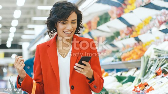 At the Supermarket: Portrait of a Beautiful Happy Young Woman Uses Smartphone While Standing at the Fresh Produce Section of the Store.