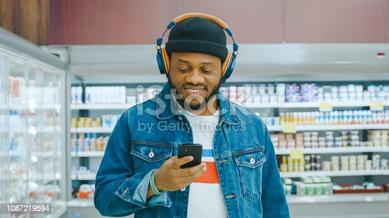At the Supermarket: Portrait of a Stylish African American Guy with Headphones, Using Smartphone, Walks Through Frozen Goods Section of the Store.