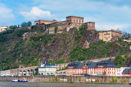 At the top of a cliff we see the Ehrenbreitstein Fortress - a UNESCO World Heritage Site in Upper Middle Rhine Valley - overlooks the east bank of the Rhine River in Koblenz, Germany