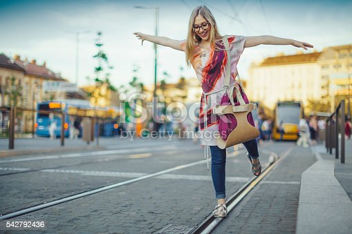 Playful young woman is at the tram station