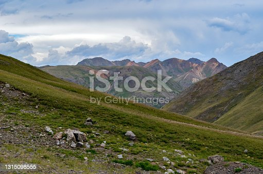 At the top of Cinnamon Pass, 12640 feet with Red top mountain to the west - Summer mountain landscape on a southwestern Colorado, USA dirt, gravel and rock backroad. This scene is near Silverton, and ghost town Animas Forks. Colorado in western USA. This is a former gold mining road. Some of the roads are 4x4.