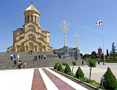 Tbilisi, Georgia - May 3, 2013: Low angle view of the Holy Trinity Cathedral with the park around it in old part of Tbilisi. In front is path to the steps with a lot of people going to the church during Georgia Eastern time. On right side there are big modern lamps and further right is Georgia flag.  In background is blue sky.