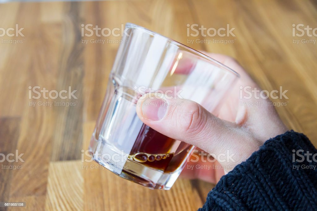 At wooden table man's hand holding glass with alcohol. First-person view royalty-free stock photo