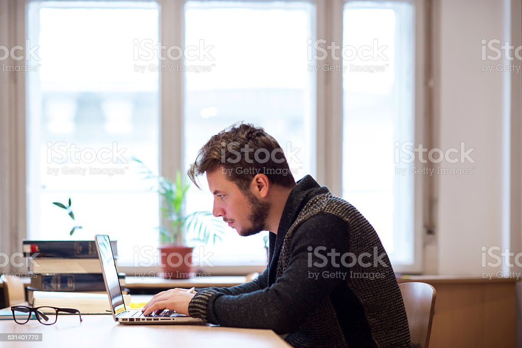 At work Man working on laptop in office 20-29 Years Stock Photo
