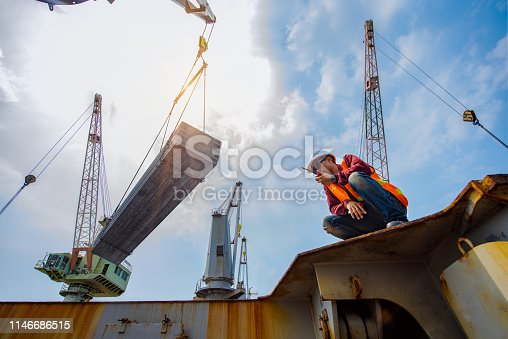 shipment steel slab being handle loading by foreman, engineering, port master or harbor loading master, working in high level and at risk of work and insurance