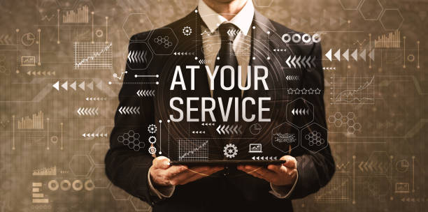at your service with businessman holding a tablet computer - обслуживание стоковые фото и изображения