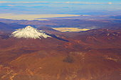 Atacama Desert – Chilean, Argentinean and Bolivian Andes aerial view – above dramatic snowcapped pastel colored landscapes, exotic volcanoes and Idyllic Atacama Desert, Volcanic landscape panorama –  Chile, Bolivia and Argentina border