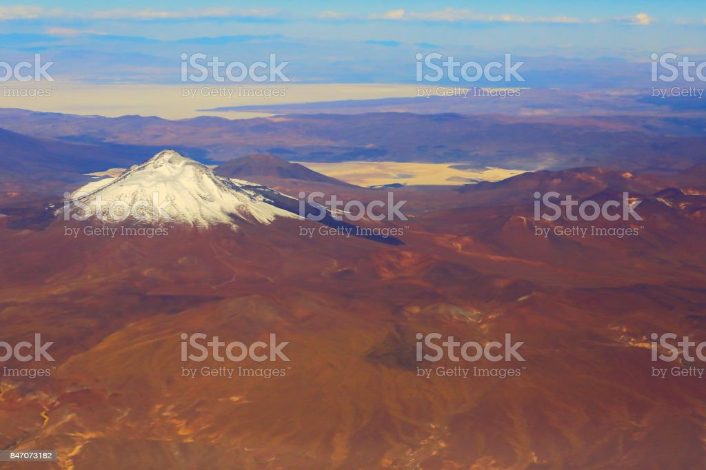 Atacama Desert – Chilean, Argentinean and Bolivian Andes aerial view – above dramatic snowcapped pastel colored landscapes, exotic volcanoes and Idyllic Atacama Desert, Volcanic landscape panorama –  Chile, Bolivia and Argentina border stock photo