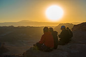 Tourists and backpackers enjoying the sunset over the Atacama desert and the Moon Valley from a cliff near San Pedro de Atacama, Chile.
