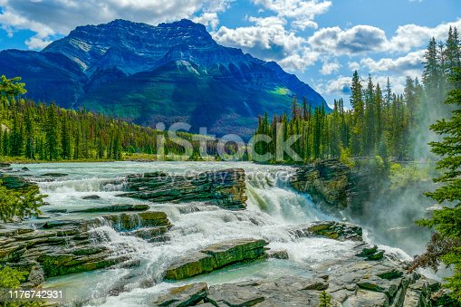 The powerful and picturesque Athabasca Falls lies on the upper Athabasca River, just west of the Icefields Parkway, in Jasper National Park, Alberta, Canada. This Class 5 waterfall pours over hard quartzite through limestone, carving out a gorge below. Mount Kerskelin lies in the background.