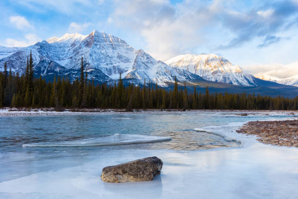 athabasca river and canadian rockies in winter at jasper national park, canada - snowy mountains stock photos and pictures
