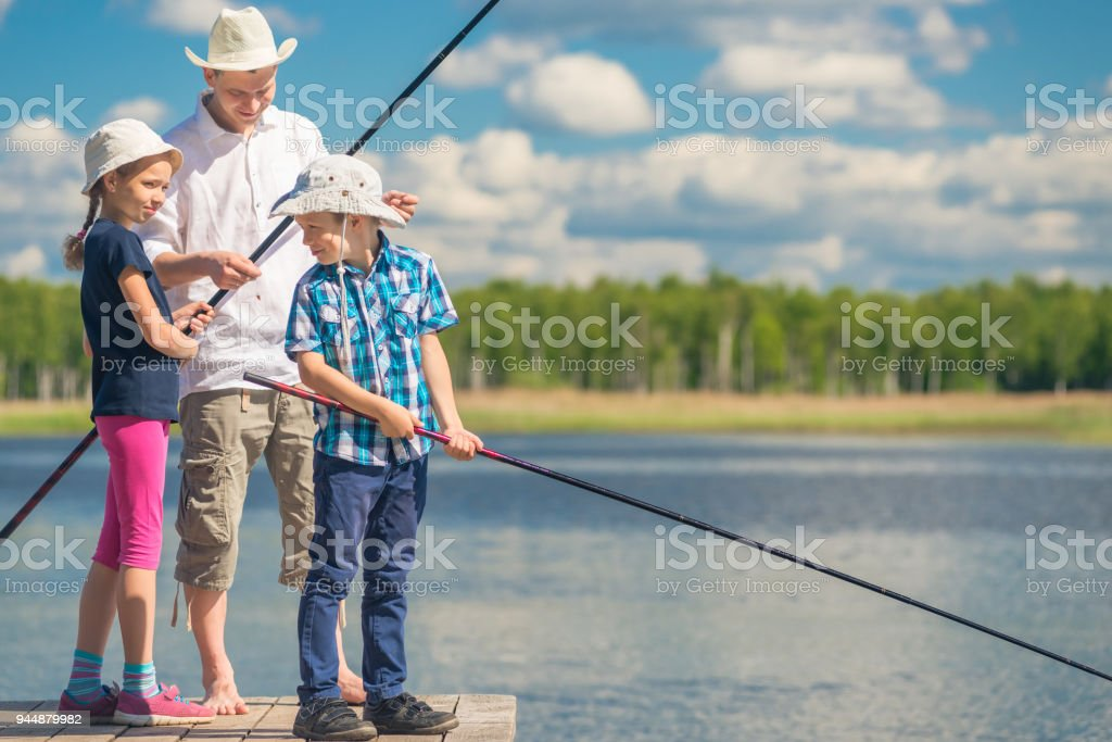 ather teaches children to fish big fish stock photo