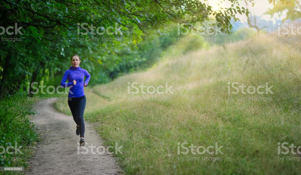 athleic jogger in a black sports leggins and and blue jacket  fast runs along the path  on the  beautiful green forest stock photo
