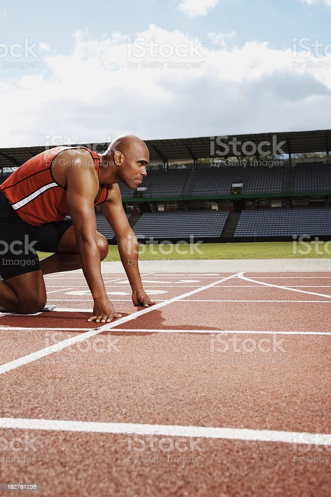 Athlete at starting line of running track royalty-free stock photo