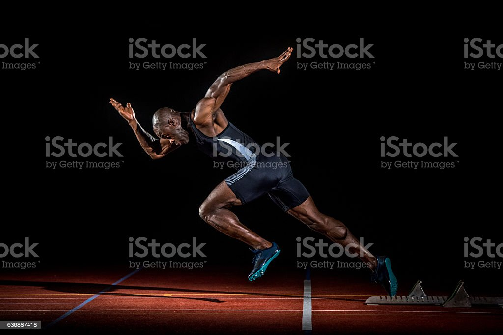 Athlete at starting line Young male athlete taking off from starting block. 25-29 Years Stock Photo