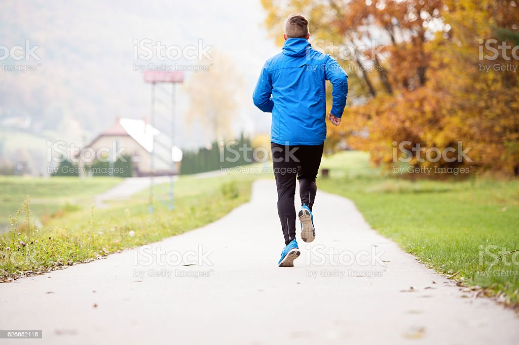 Athlete at the lake running on concrete path, rear view. royalty-free stock photo