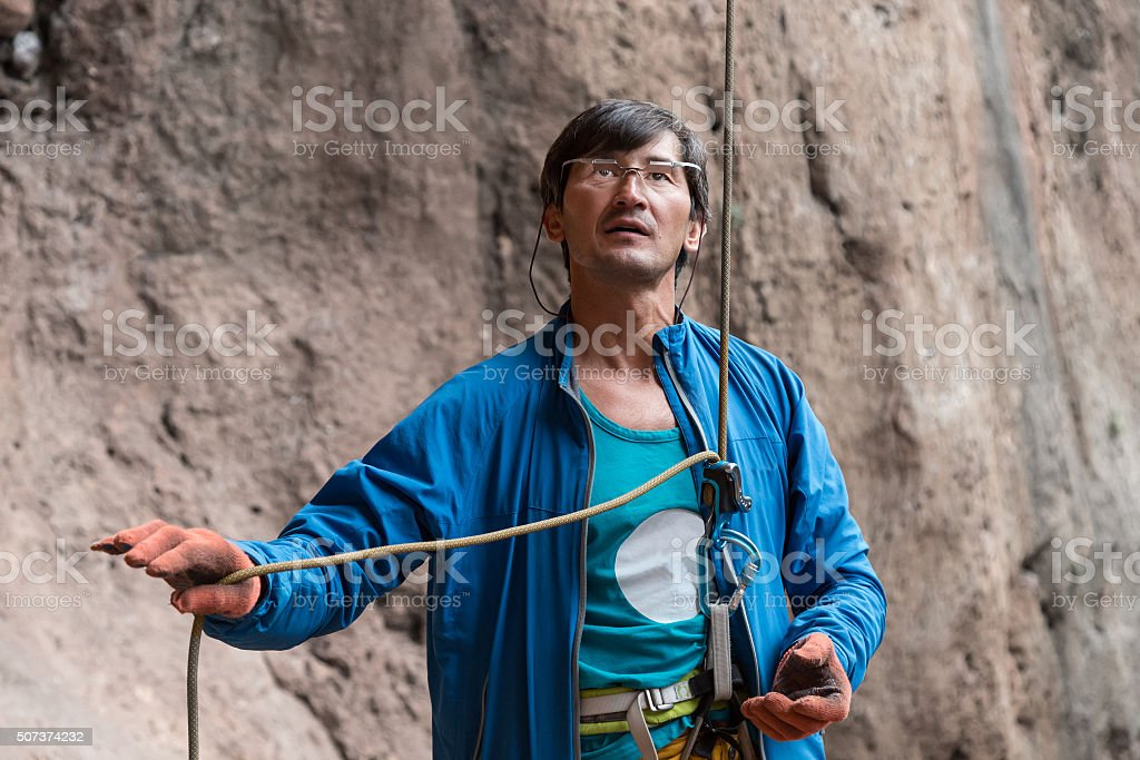 Athlete belays Climber using belaying device and rope stock photo