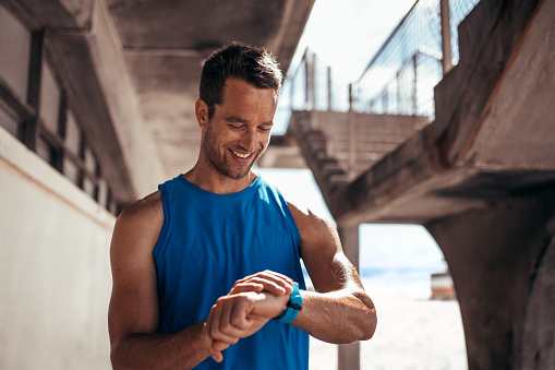 Athlete checking his progress on smartwatch fitness app