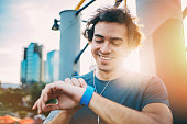 Young man in sports wear looking at his smart watch outdoors at urban setting