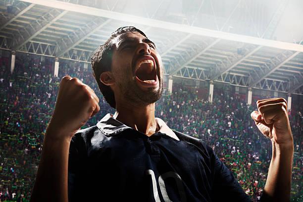 athlete cheering with excitement in sports stadium arena - gute nacht text stock-fotos und bilder