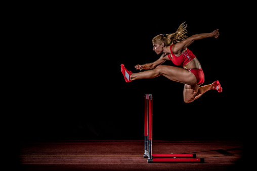 Female athlete jumping over hurdle.