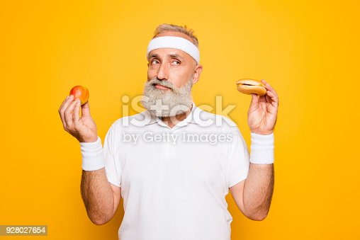 istock Athlete cool grandpa holds forbidden junkfood cheeseburger and fruit. Weightloss, decision, motivation, healthcare, strength, prohibition, workout, gym, regime, bodycare, calories lifestyle 928027654