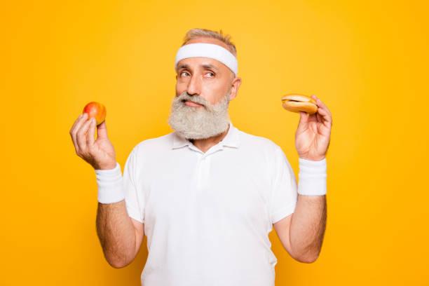 athlet cool opa hält verbotene junkfood cheeseburger und obst. weightloss, entscheidung, motivation, gesundheitswesen, stärke, verbot, training, fitness-studio, regime, bodycare, kalorien lebensstil - gesundheitsfragen stock-fotos und bilder