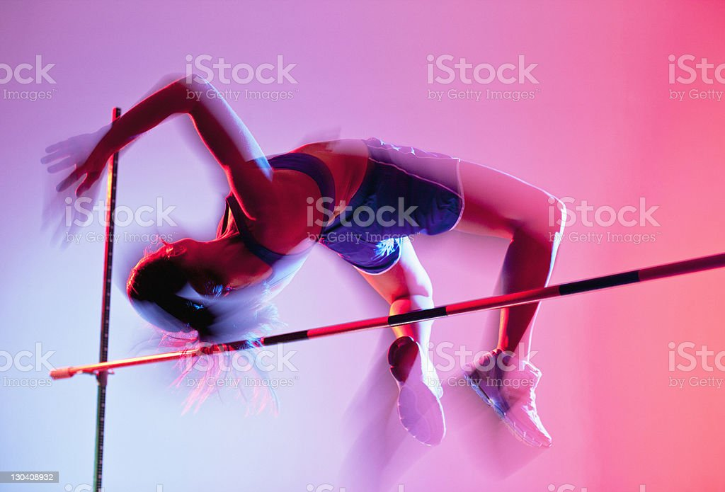 Athlete curling over high jump stock photo