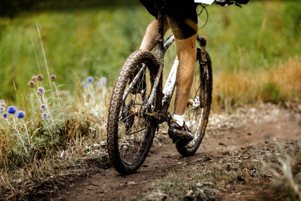 athlete cyclist dirty mountain bike biking in trail - mountain biking stock pictures, royalty-free photos & images