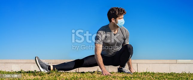 istock athlete does muscle stretching with sanitary face mask 1268749811