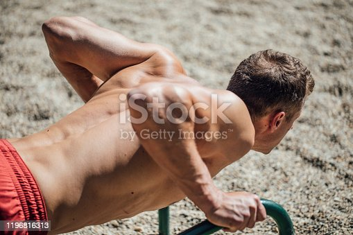 Muscular Caucasian man doing a push-up on the outdoor push-up bars.