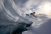 Athlete doing a step up jump on a snowmobile
