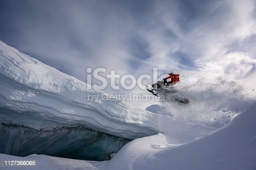 Snowmobiler jumping in the mountains