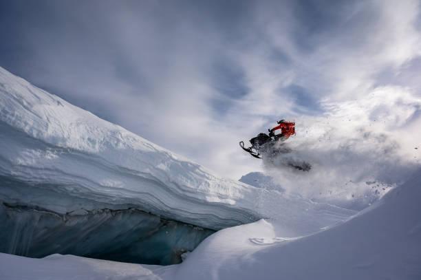 Sportler machen einen Schritt nach oben springen auf einem Schneemobil – Foto