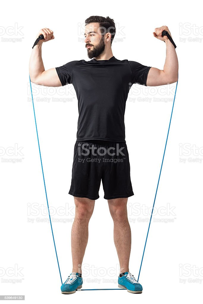Athlete doing arms and shoulders exercise with resistance elastic bands stock photo
