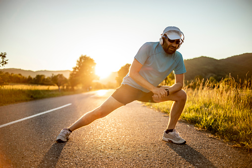 Athlete doing exercises on the road in nature - An athlete who runs outdoors for exercise and fitness - Athletic Man Doing Running
