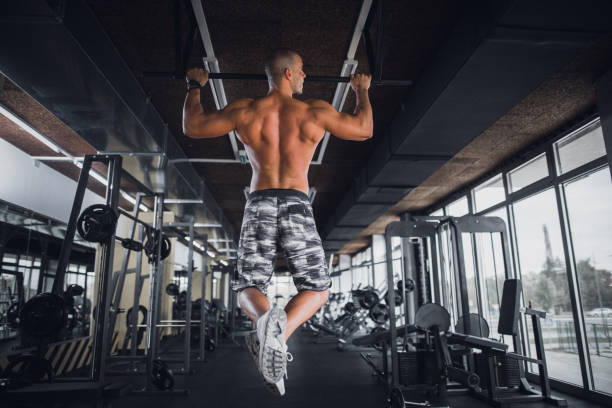 athlete doing pull-up on horizontal bar - horizontal bar stock photos and pictures