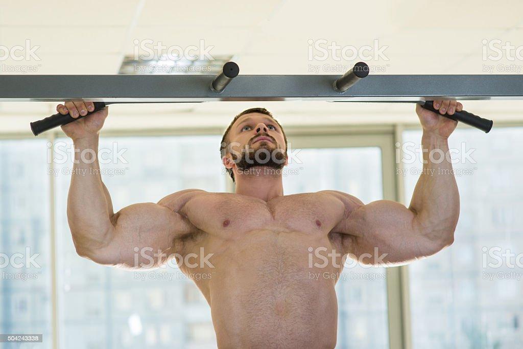 Athlete doing pull-ups stock photo