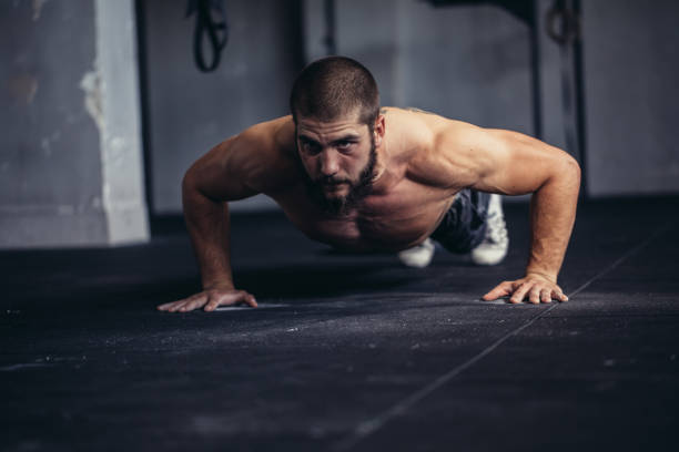 athlete doing push-ups - push up stock photos and pictures