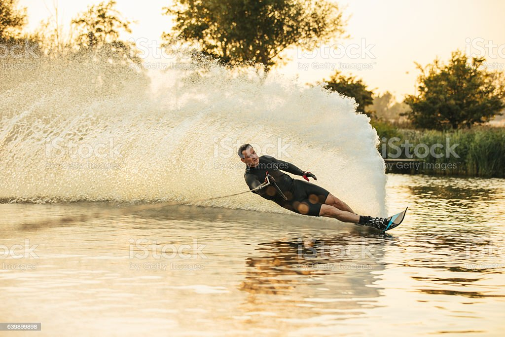 Athlete doing stunts on wakeboard in lake stock photo