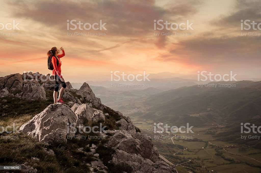 Athlete Drinking Water on the Top of the Hill stock photo