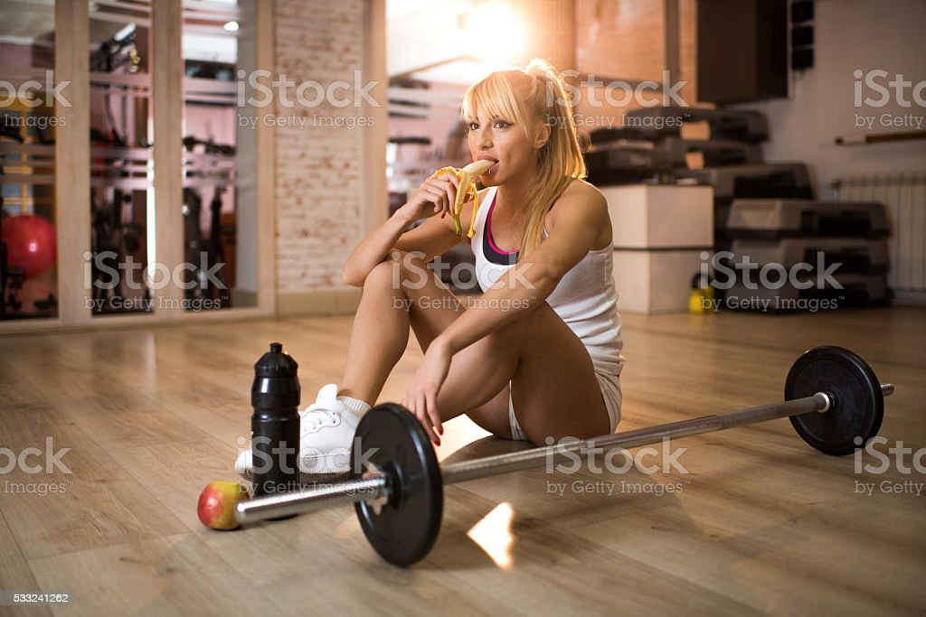 Athlete eating banana on a break in a gym. stock photo
