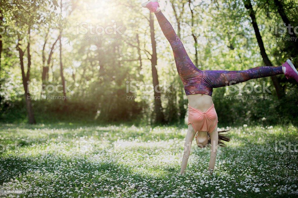 athlete female makes a cartwheeling - front stock photo