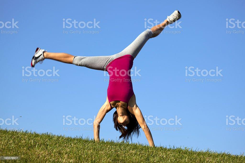 Athlete Girl Doing Cartwheels on Hilltop stock photo
