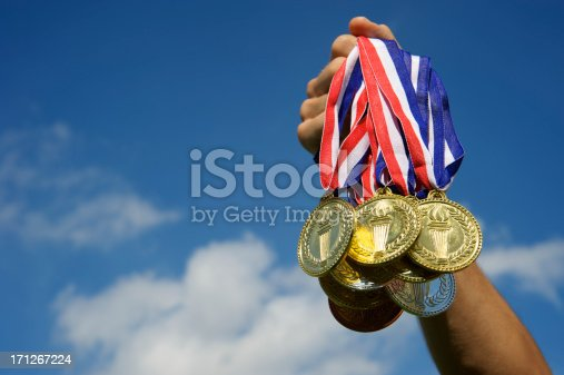 istock Athlete Hand Holding Up Bunch of Gold Medals Blue Sky 171267224