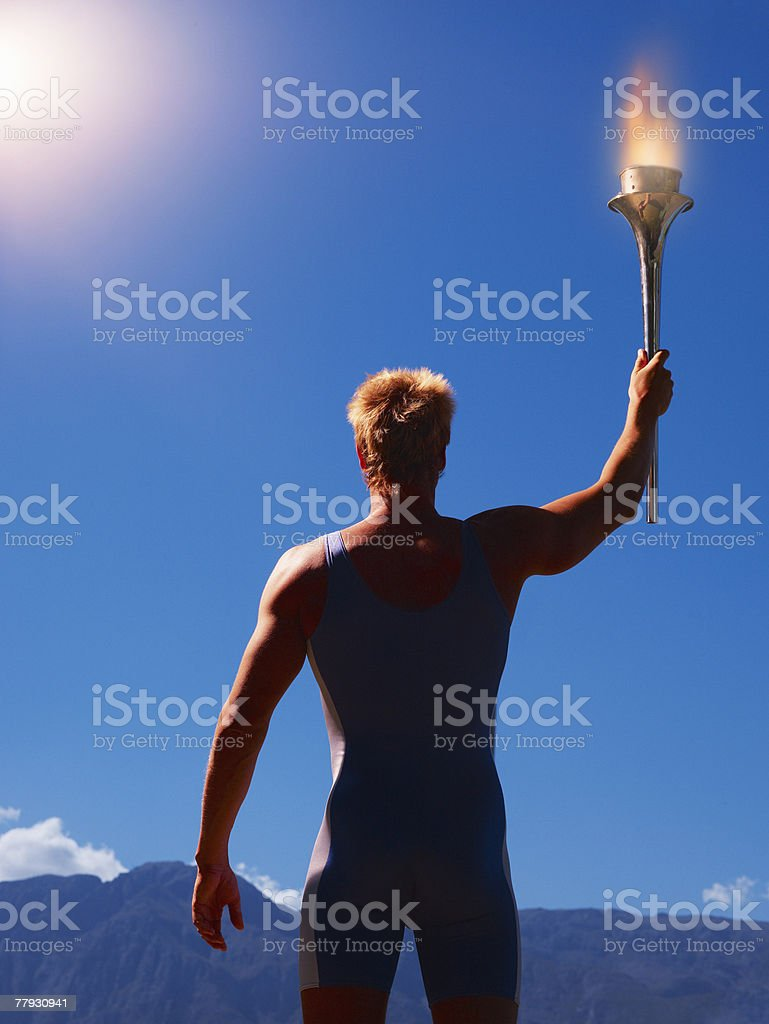 Athlete holding torch in scenic location stock photo